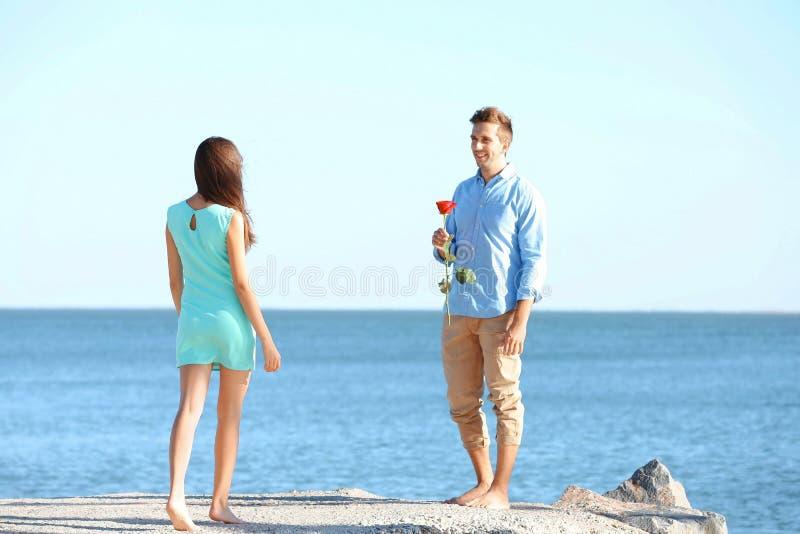 Dare del giovane è aumentato alla sua amica vicino al mare fotografia stock