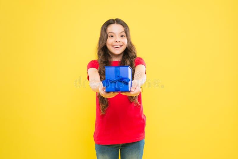 Dare del regalo la rende felice Bambina adorabile che dà scatola attuale blu su fondo giallo Il piccolo bambino sveglio gode di fotografie stock