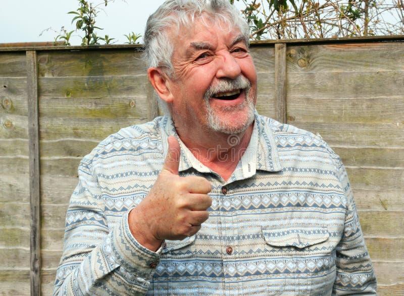 Dare felice dell'uomo senior sfoglia sul segno. immagini stock libere da diritti
