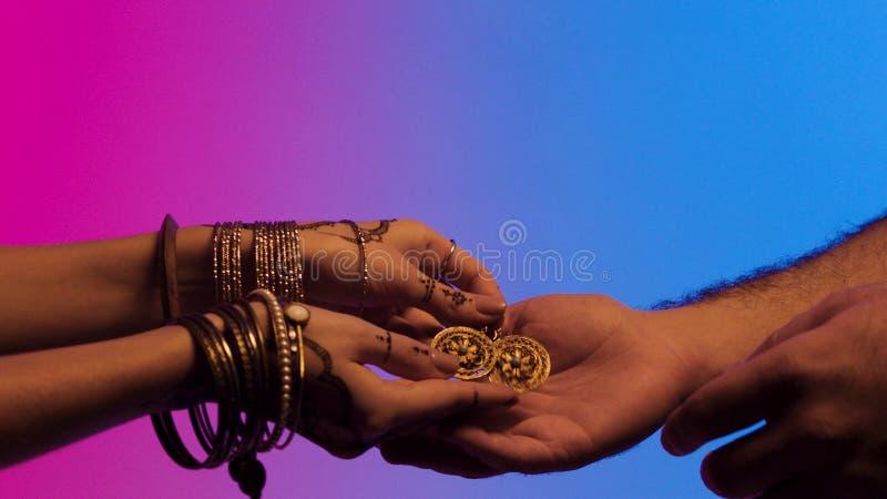 Dare femminile dorato, orecchini fatti a mano orientali e d'annata su un fondo colourful, gioielli antichi delle mani di mehendi fotografia stock