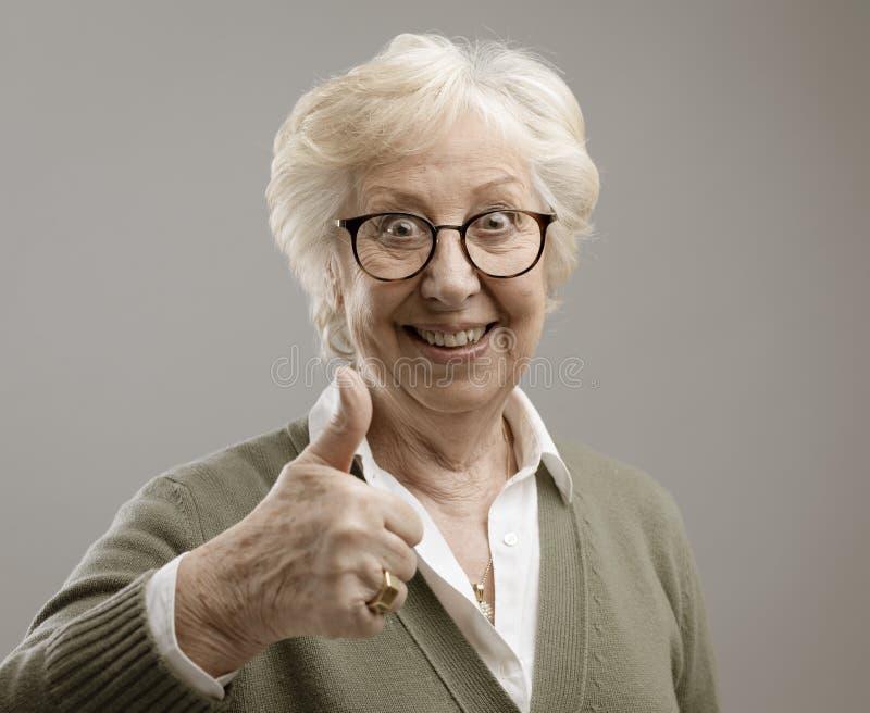 Dare senior allegro di signora pollici su fotografie stock libere da diritti