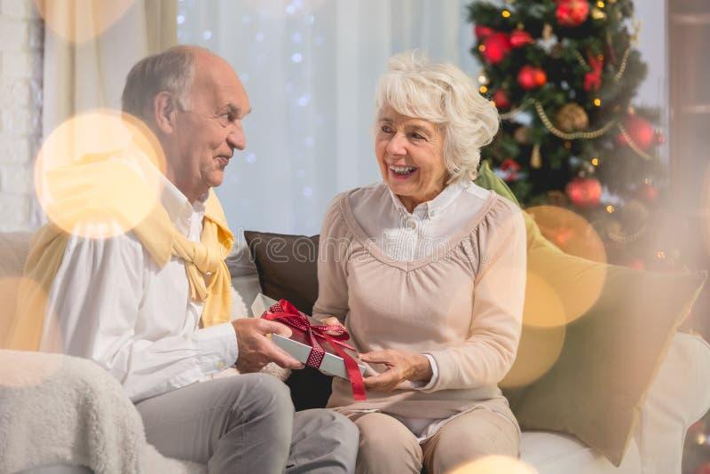 Dare senior della persona femminile presente al suo marito immagine stock