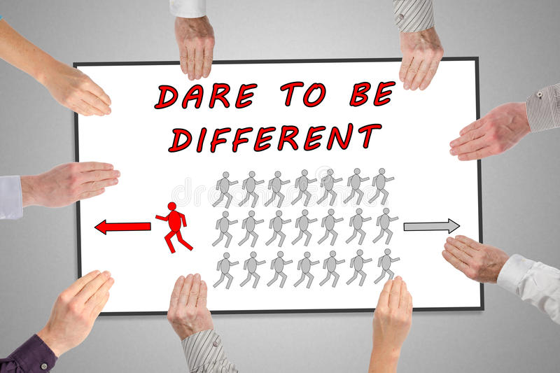 Dare to be different concept on a whiteboard. Held by hands stock image