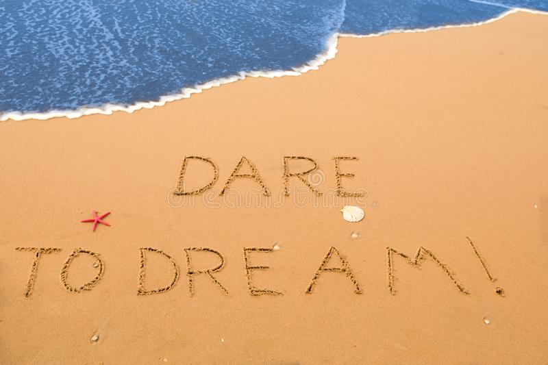 Dare to dream written in the sand stock photography