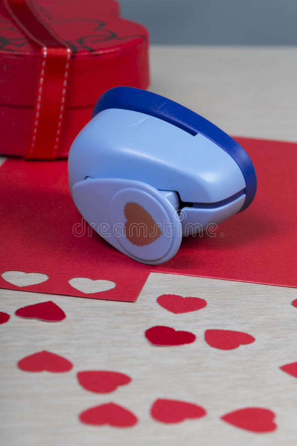 Dargestellter Plastikpapierdurchschlag und handgemachte rote Herzen stockfoto