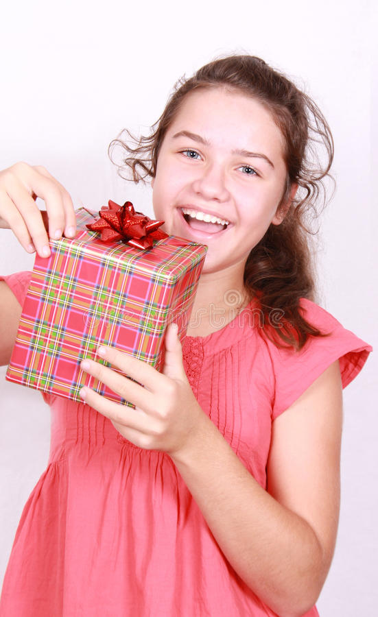 Daring girl opens gift. Girl of the school age opens gift stock images