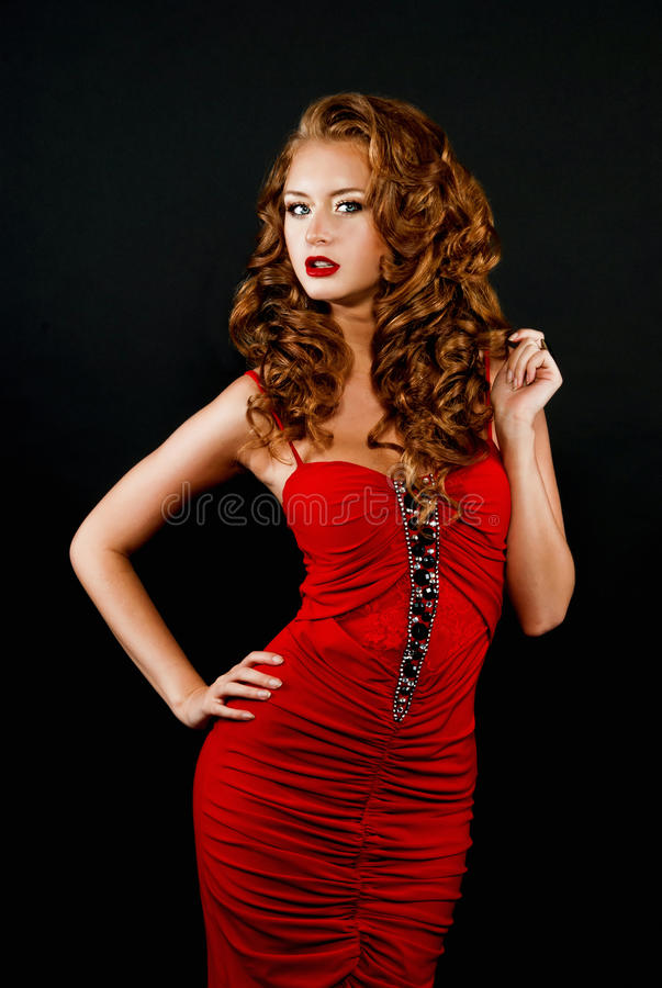 Daring Red-haired Girl In A Red Dress Royalty Free Stock Photos