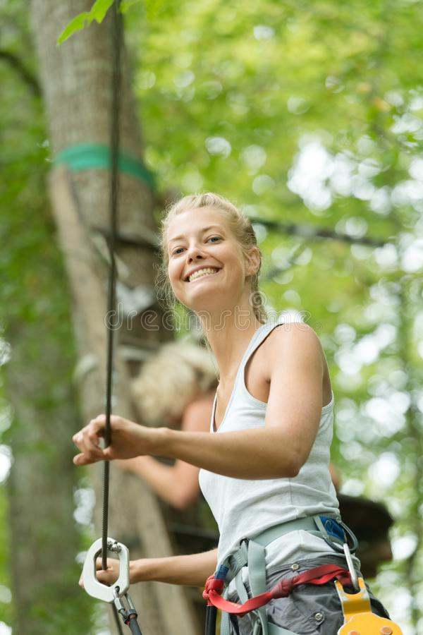 Daring woman wearing harness strapped to zip wire in trees. Woman royalty free stock photos