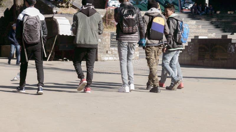 Darjeeling, Inde - mai 2018 : Groupe d'amis de sourire marchant sur la route au temps de jour Vue arri?re Image cultiv?e Les gens image stock