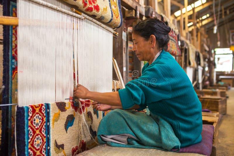 Unidentified tibetan woman works as weaver in the carpet workshop of Tibetan Refugee Self Help Center, Darjeeling, India stock image