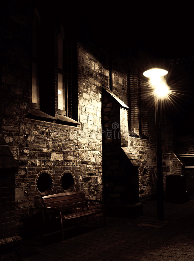 Dark Alley. A bench in a dark alley way illuminated by a lamp post royalty free stock image