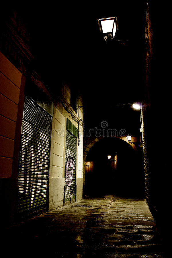 Dark alley in the city. A picture of a quiet and dark alley, with graffiti on the walls and dim street lights overhead stock image
