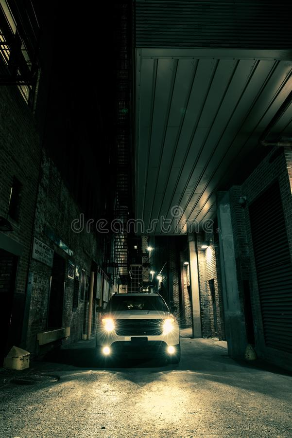 Dark Alley Drive. American City at Night. SUV on the Alley stock images