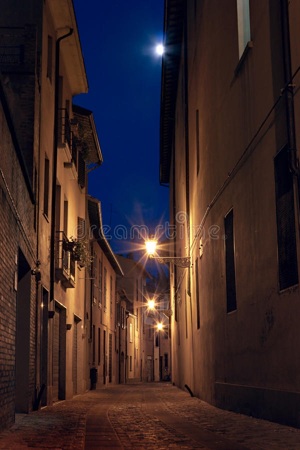 Dark alley in the old town. Narrow dark alley in the old town -street at night in the Italian city lit by streetlights and the moon - romantic cityscape in royalty free stock photography
