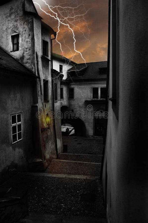 Dark alley scenery. A dark alley way illuminated by a lamp post and a lightning hitting a house stock image