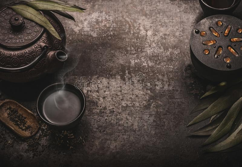 Dark asian tea background with black iron teapot and mug of green tea. Copy space for your design. Authentic vintage style stock photography