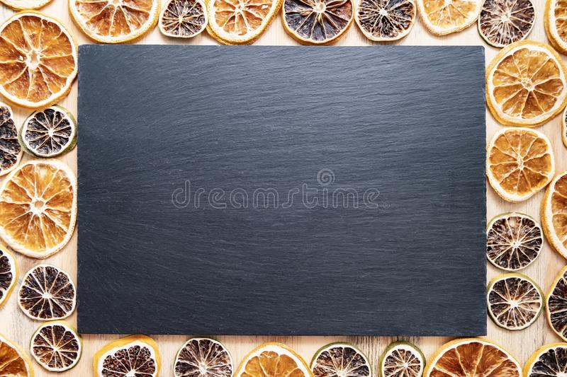 A dark background of a slate board and dried citrus fruits lemon, lime and orange for decoration are on a wooden table, with stock photography