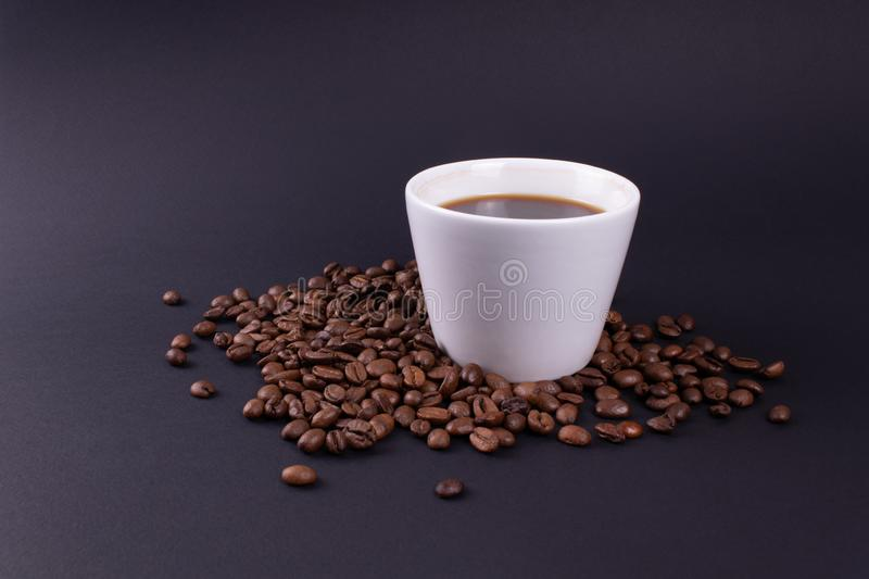 On a dark background a white mug of strong coffee in coffee beans royalty free stock photography