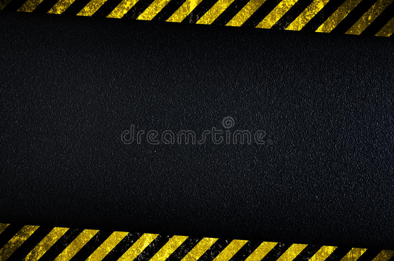 Dark background with yellow caution stripes royalty free stock images