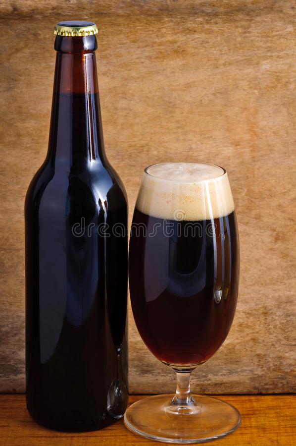 Dark beer. Glass and bottle of dark beer on a wooden background stock photography