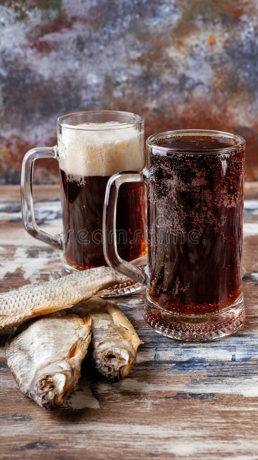 Dark beer in glass mugs and dried fish on a wooden table. Vertical shot stock image