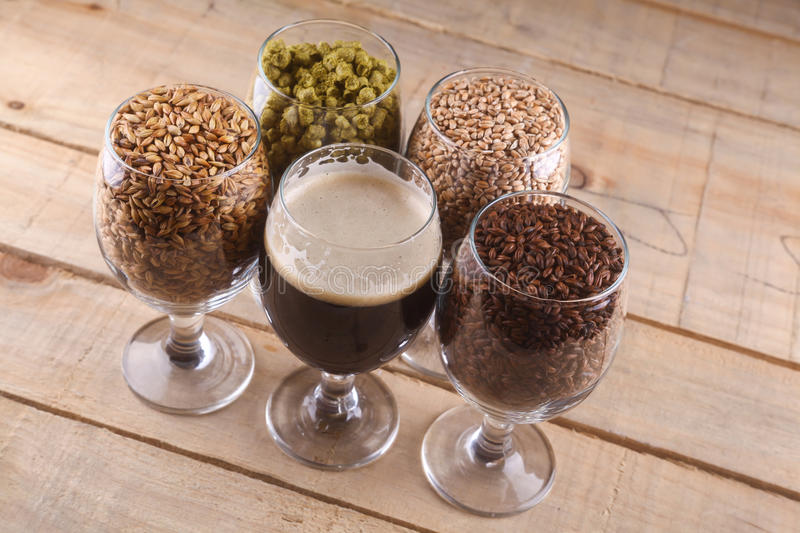 Dark beer and ingredients. Glasses filled with dark beer, different malts and hops over a wooden background royalty free stock image