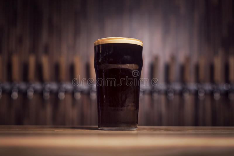 Dark beer in a large beer mug stands on the bar royalty free stock image