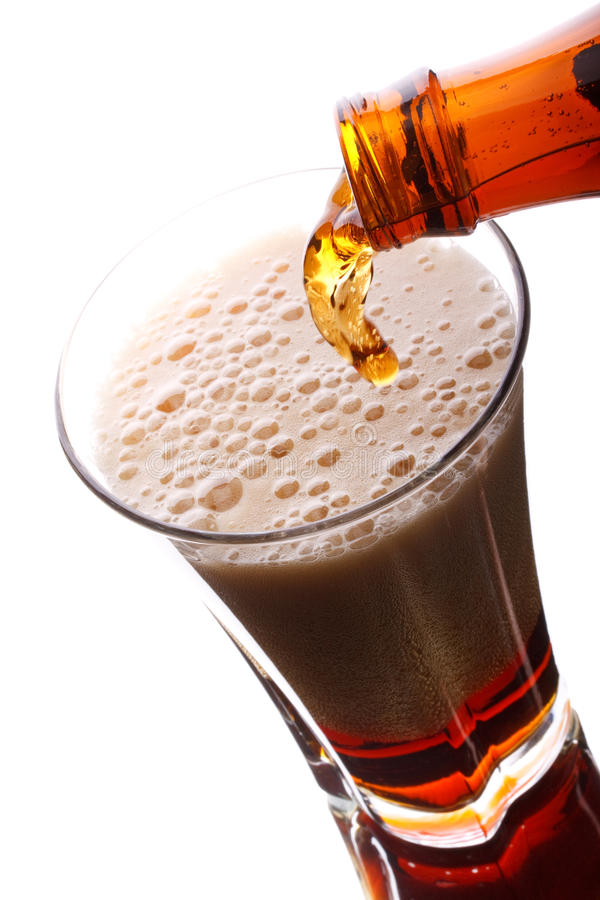 Dark beer pouring. Into glass on a white background stock photography