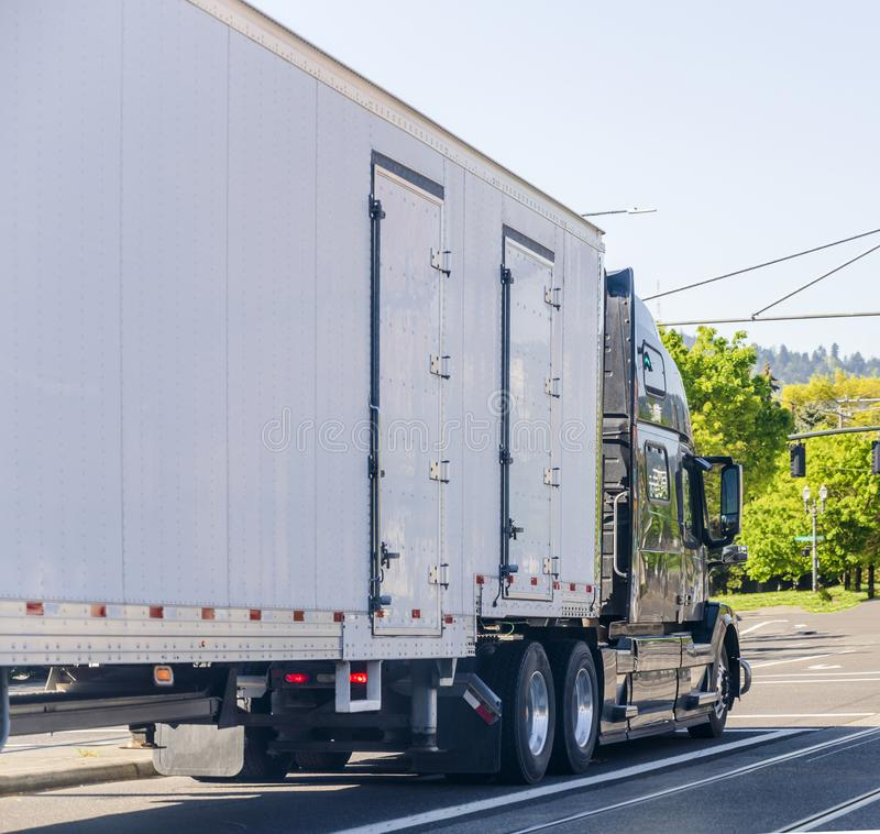 Dark big rig long haul semi truck transporting commercial cargo in covered semi trailer driving on the city street. Dark big rig long haul professional stock photography