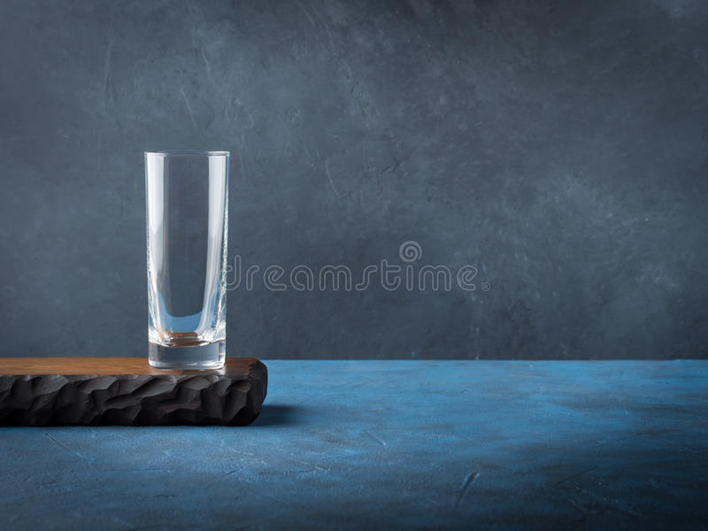 Dark black background with empty glass on wooden board stock image