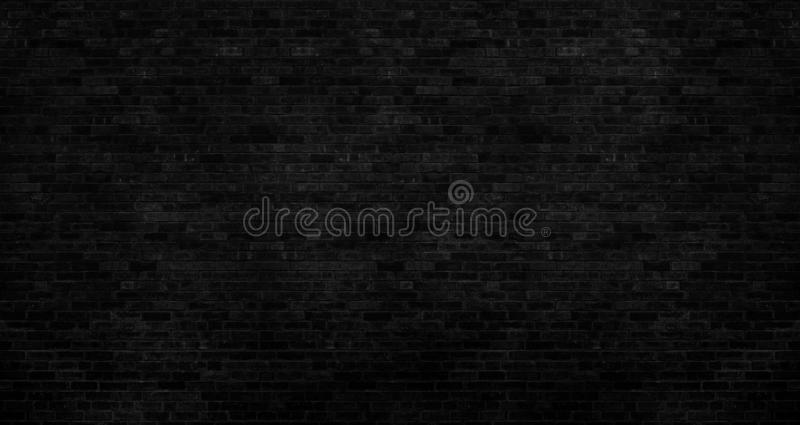 dark black brick wall has a rough surface as a background image stock image