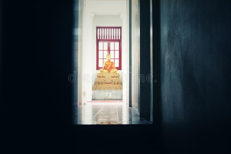The dark black interior has a number of gilded golden Buddha statues, and the back has red colored windows. And light through royalty free stock photography