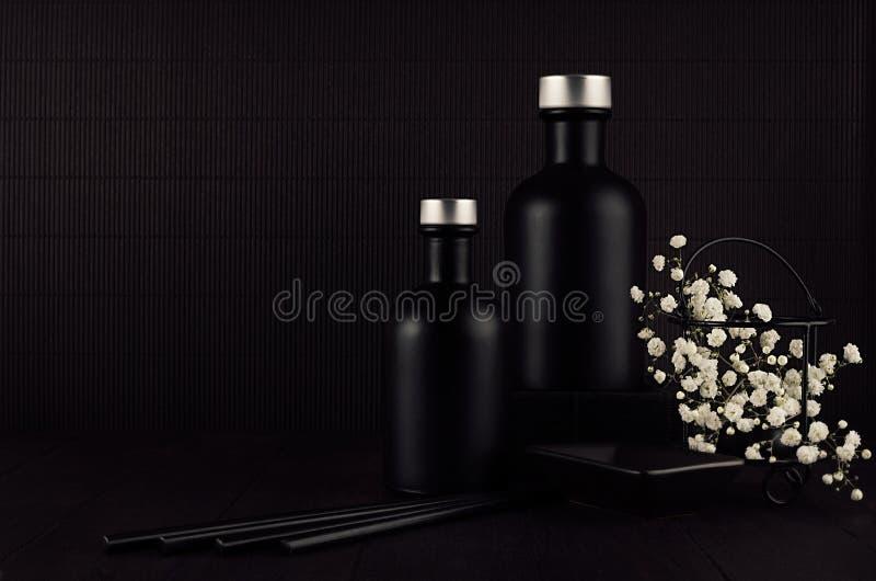 Dark black minimalist interior with blank black bottles, white small flowers on dark wood board, mock up. stock photo