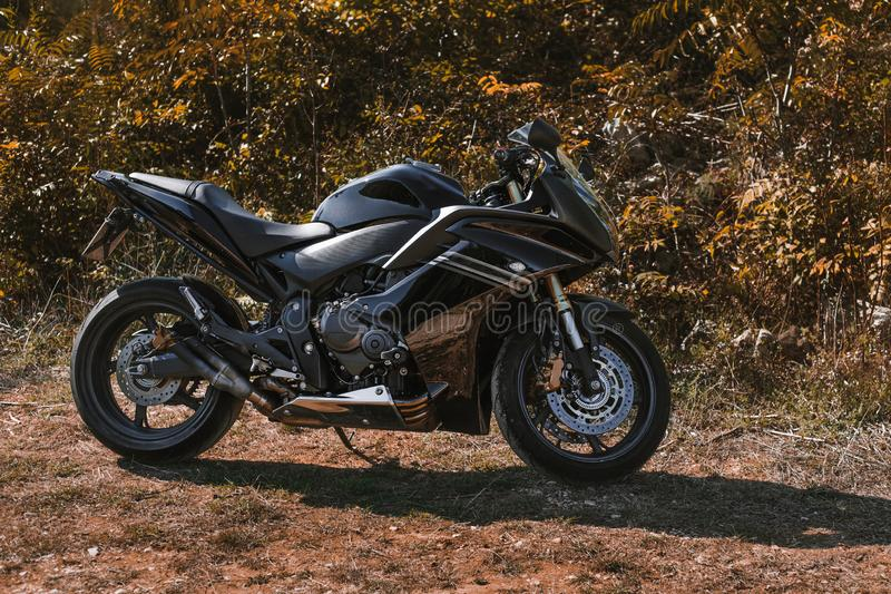 Dark Black sport motorcycle without logo and rider standing on the grass in forest on sunny day. Power motorbike parking on the stock photo