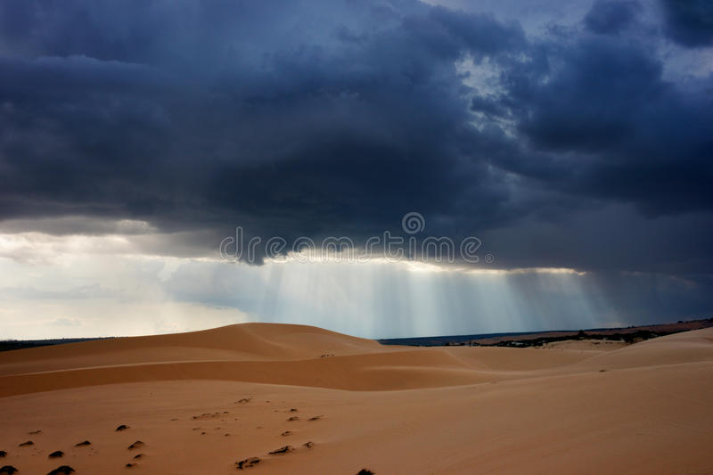 Dark black storm clouds with piercing sunrays covering desert landscape. stock image