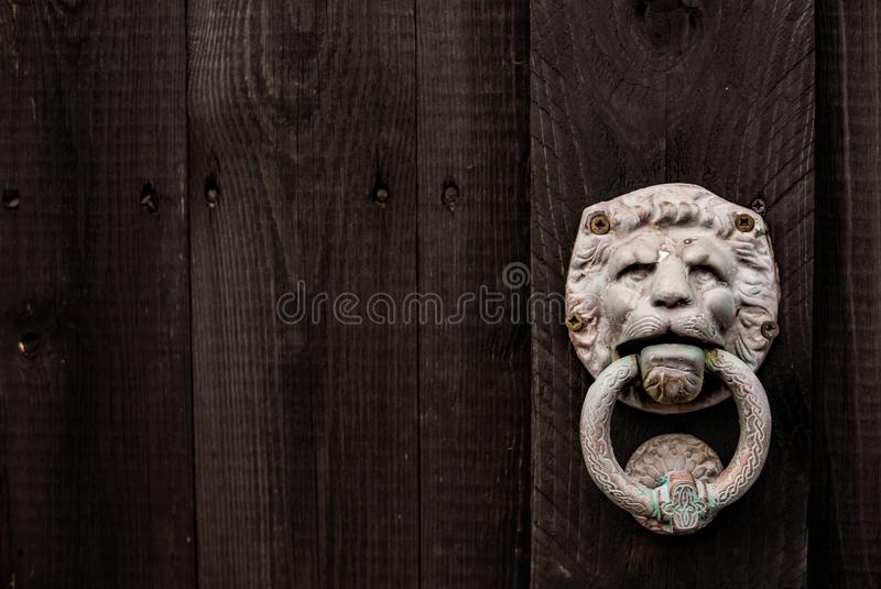 Dark black wooden background with lion shaped door knocker and s stock photography