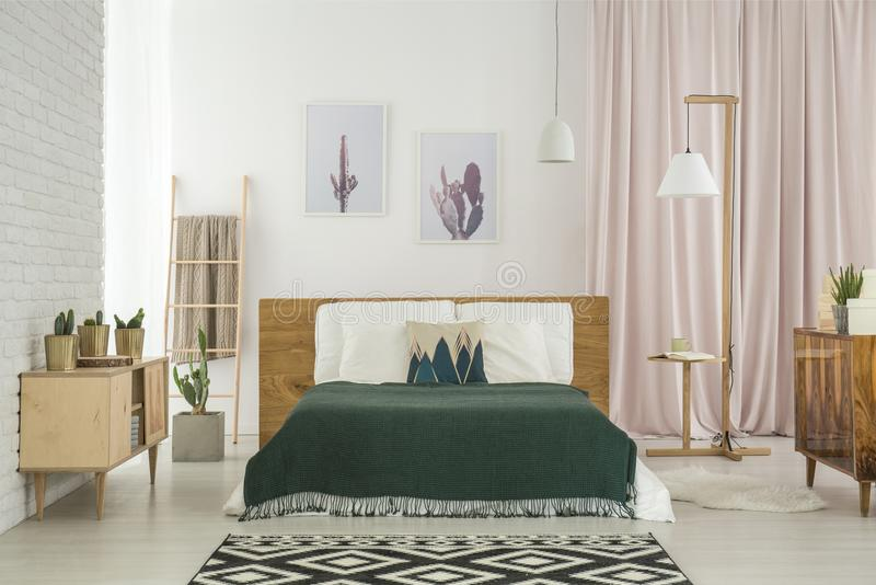 Rustic bedroom with wooden furniture. Dark blanket on king-size bed and geometric carpet in rustic bedroom with wooden furniture stock photo