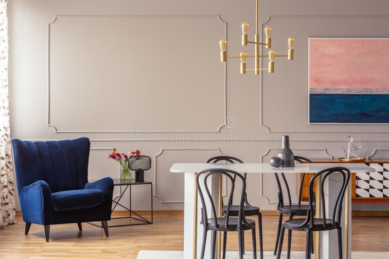 Dark blue armchair in a dining room interior with a table, chairs and golden lamp stock photos