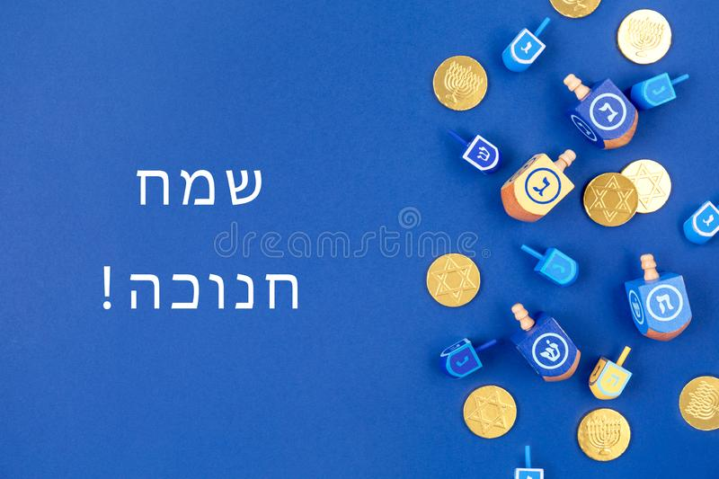Dark blue background with multicolor dreidels and chocolate coins and Happy Hanukkah wording in Hebrew. Dark blue background with dreidels and chocolate coins stock photos