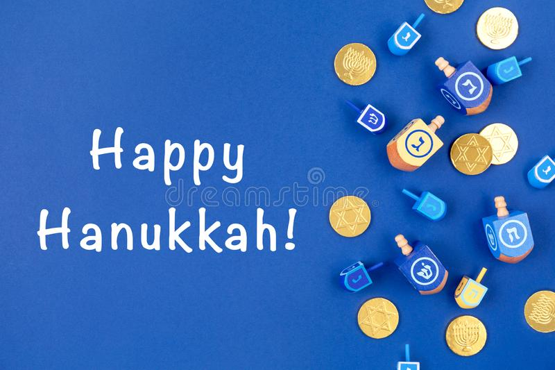 Dark blue background with dreidels and chocolate coins and Happy Hanukkah wording. Hanukkah and judaic holiday concept. Dark blue background with multicolor royalty free stock image