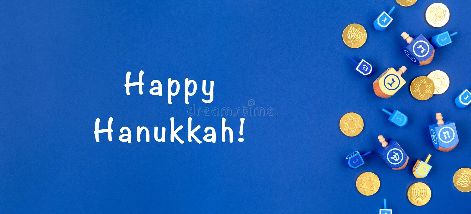 Dark blue background with dreidels and chocolate coins and Happy Hanukkah wording. Hanukkah and judaic holiday concept. Dark blue background with multicolor royalty free stock photography