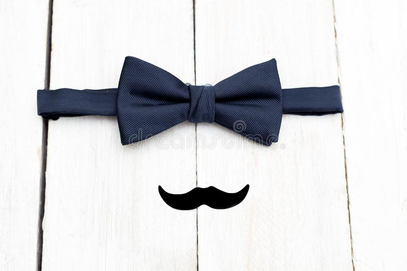 Dark blue bow tie and mustache on a wooden background. Flat lay stock photography