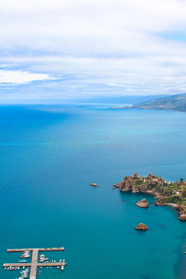 Dark blue calm water of Tyrrhenian sea surrounding the Sicilian coastal village Cefalu from above. Captured on vertical picture. With pier and boats in the sea stock image