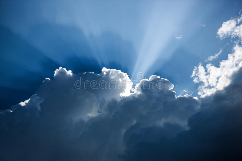 Dark blue cloud formation with sunbeams royalty free stock images