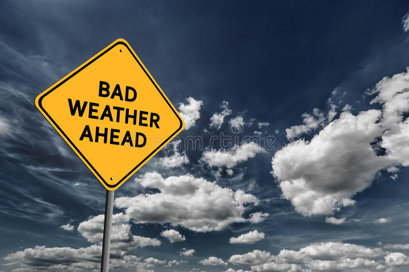 Dark blue cloudy sky and yellow road sign royalty free stock image