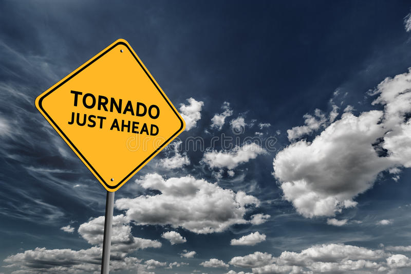 Dark blue cloudy sky and yellow road sign. Background of dark blue sky with cumulus clouds and yellow road sign with text Tornado Ahead stock photo
