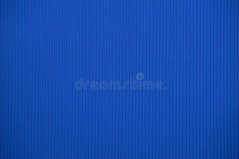 Dark blue colored corrugated cardboard texture useful as a background stock photography