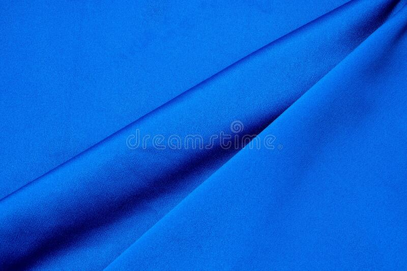 Dark blue colored fabric background. Beautiful satin silk textured fabric. Design, sewing and needlework concept royalty free stock image