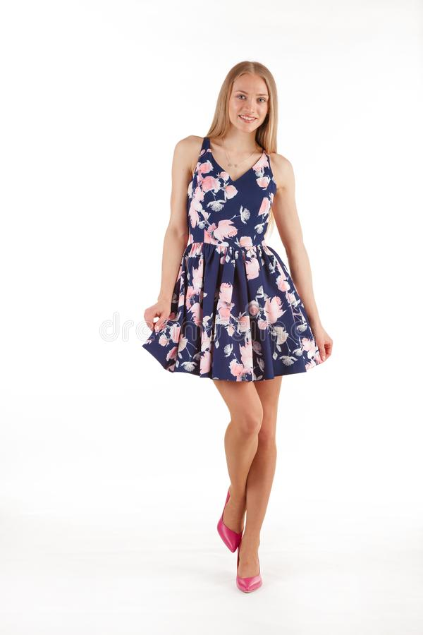 Beautiful young blonde woman in dark blue dress with floral print isolated on white background royalty free stock photos