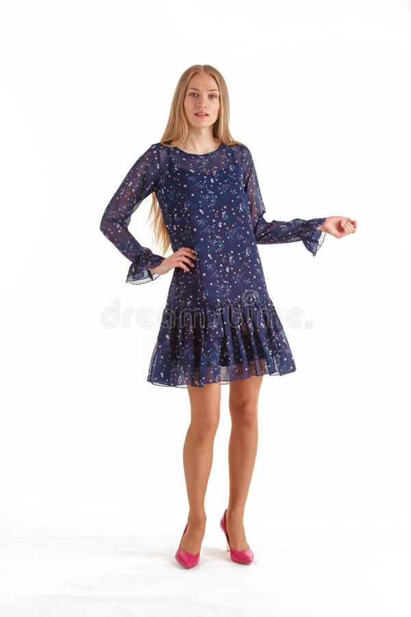 Beautiful young blonde woman in dark blue dress with floral print isolated on white background stock image